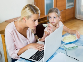 woman working from home, little daughter asking for attention
